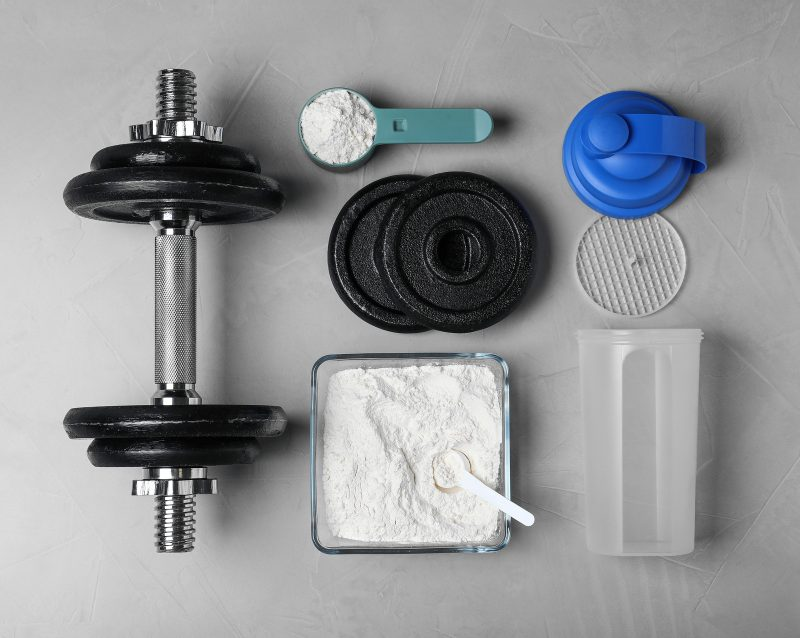 Flat Lay Composition With Protein Powder And Dumbbell On Grey Ba