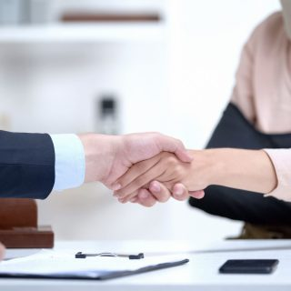 Insurance agent shaking hand with woman in arm sling, psychological support